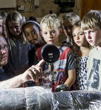 Simon Eriksen, teknisk serviceleder fra Skovlyskolen, viser elever rundt i fyrrummet. Foto: Carsten Andersen