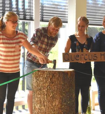 Den nye bygning er døbt 'Quercus-huset'. En gruppe studerende huggede den fede, grønne silkesnor over med økse.