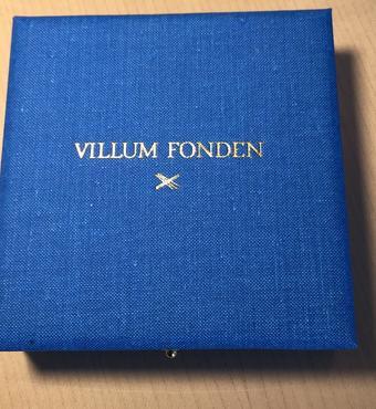 Medaljen er udført i bronzeret messing og lagt i håndlavet etui i mellemblåt vævet stof med VILLUM FONDENs navn og bomærke i guldtryk på låget.